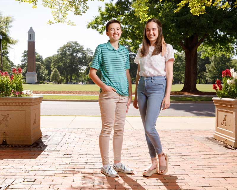Two students standing on the quad, smiling.