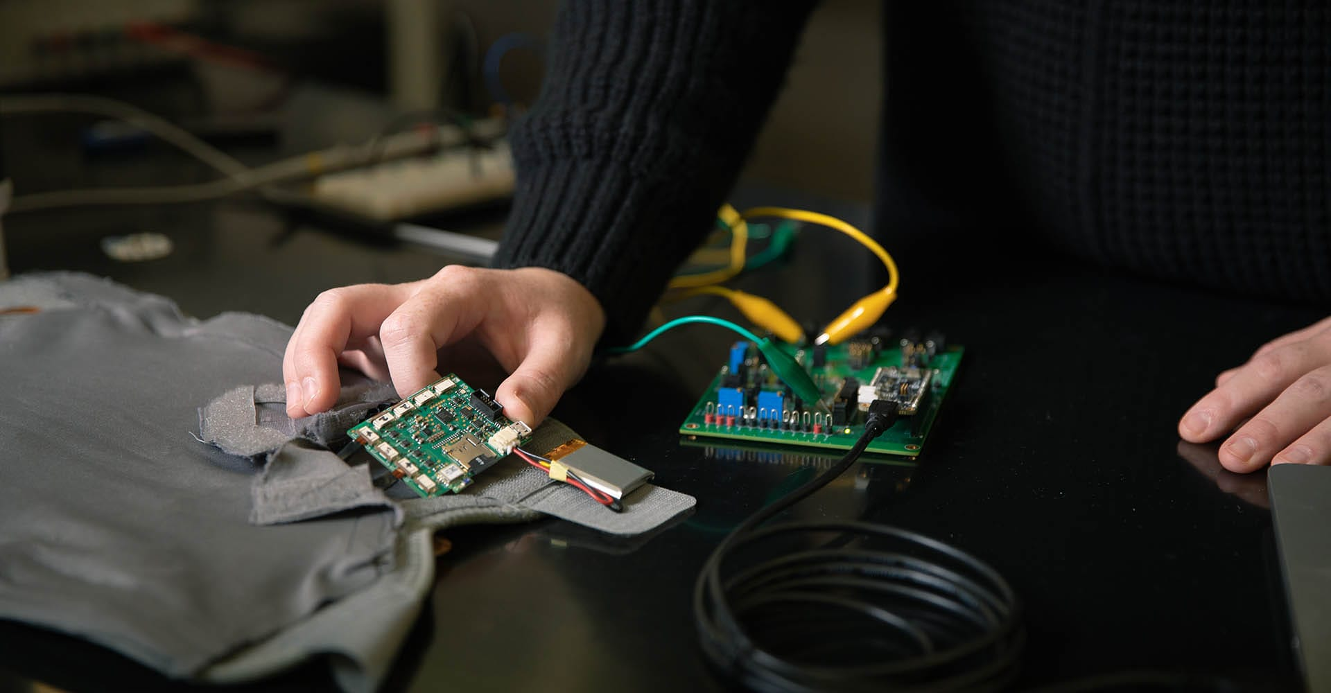 A motherboard is connected to cords as another is examined.